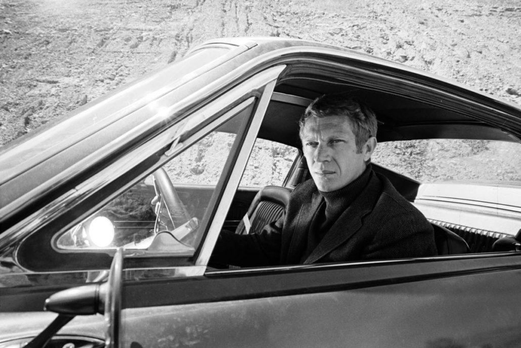 McQueen portant un col roulé monochrome avec sa veste, un style qui est de nouveau populaire en ce moment