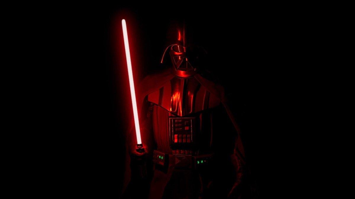 Dark Vador, debout dans une pièce d'un noir absolu éclairé par un sabre laser rouge.