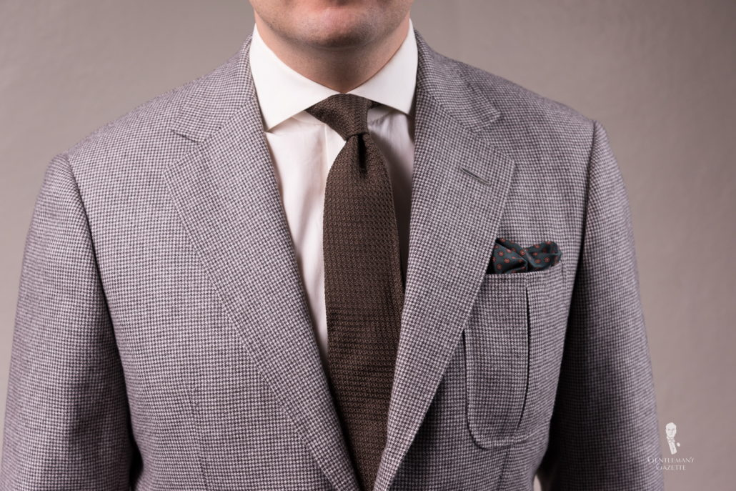 Veste pied-de-poule avec cravate grenadine marron et pochette en soie vert foncé avec motifs pois orange et cachemire bleu - Fort Belvedere