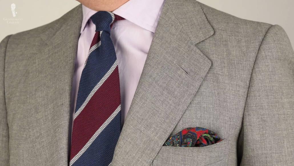 Une cravate grenadine en laine et cachemire à rayures bleu foncé, bordeaux et gris clair de Fort Belvedere, associée à un costume gris clair, une chemise lavande et un mouchoir de poche à motifs