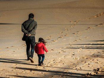 Père et fille marchant sur la plage
