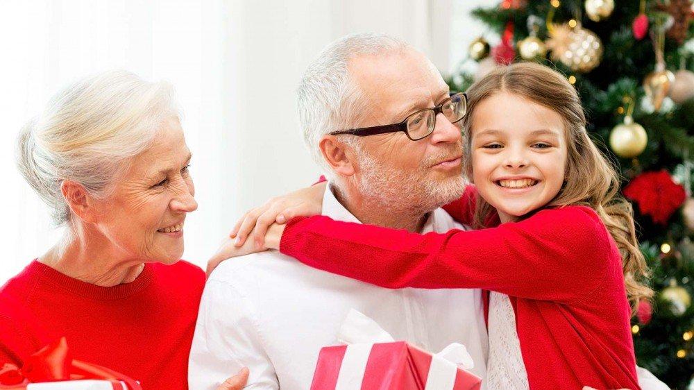 Une petite fille étreignant ses grands-parents par un arbre de Noël.