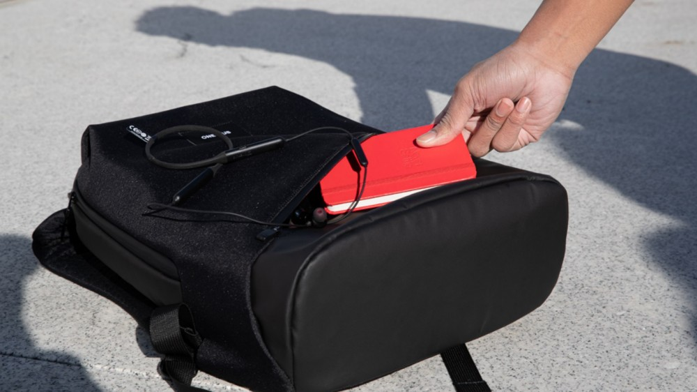Quelqu'un insère un cahier dans le sac à dos Urban Traveler.