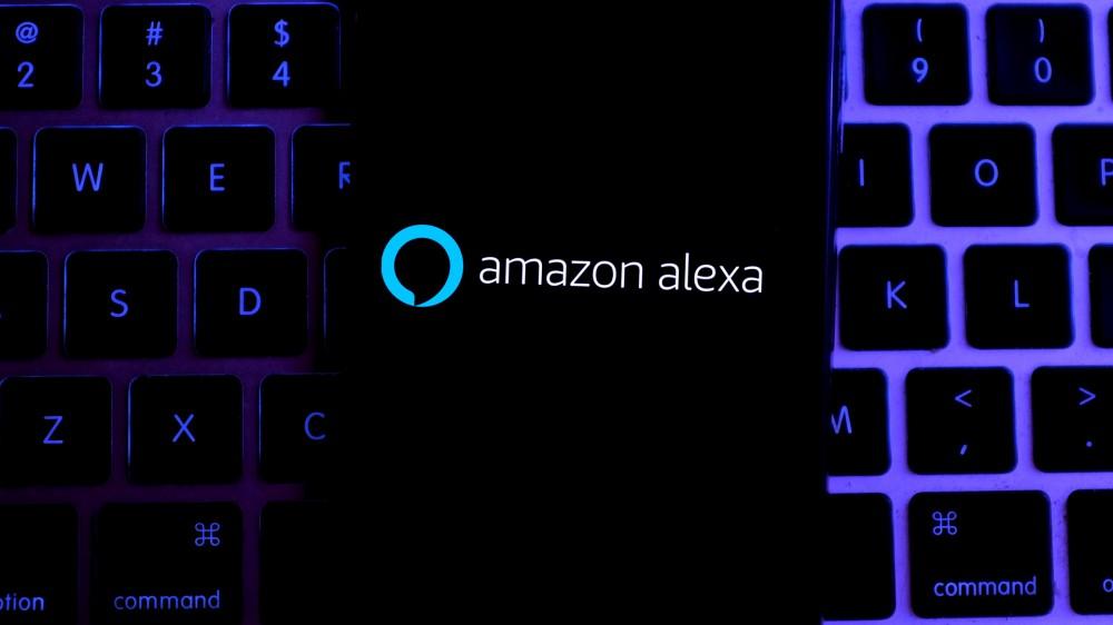 Amazon Alexa sur un iPhone reposant sur un clavier MacBook.