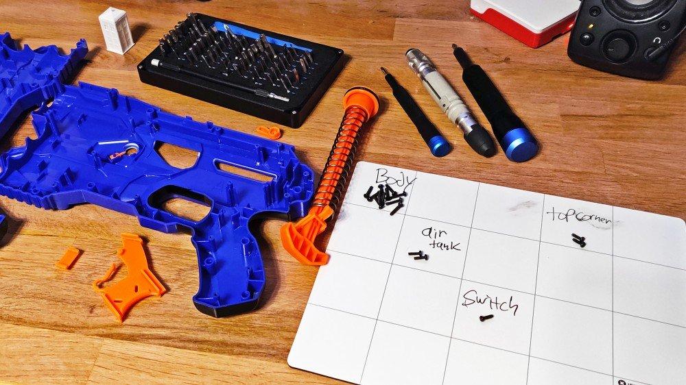 Deux kits iFixit entourés d'un pistolet Nerf déchiré.