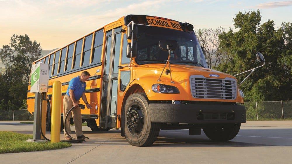 Un autobus scolaire électrique, branché sur un chargeur.