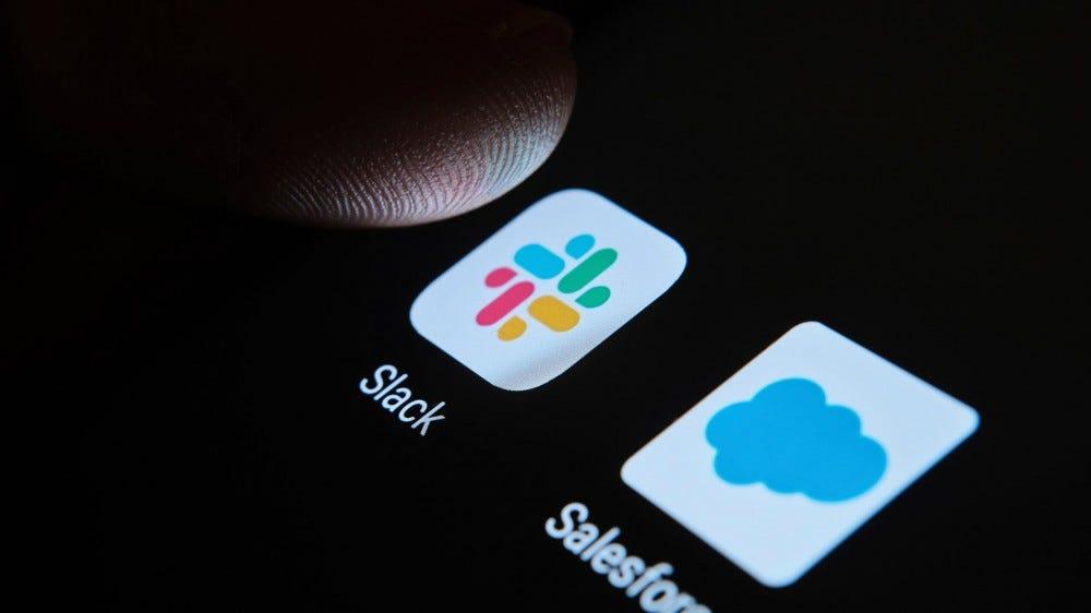 Un écran sombre avec une icône Slack et un doigt le touchant presque.