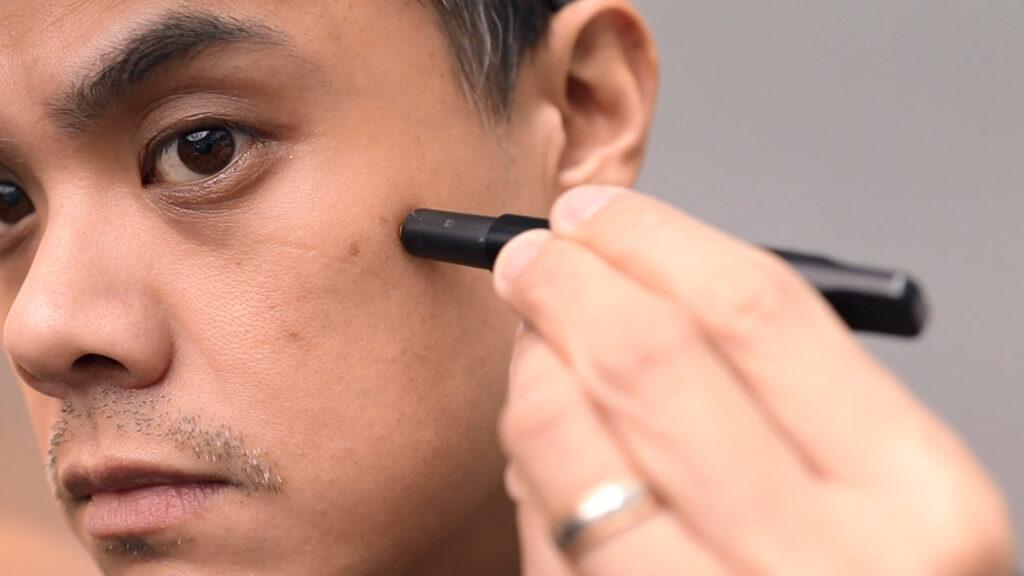 Homme appliquant un correcteur avec outil correcteur stryx