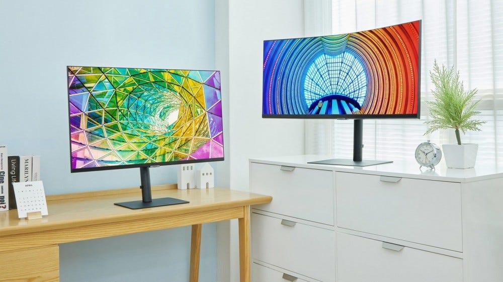 Deux nouveaux moniteurs Samsung sur un bureau en bois et un classeur en métal