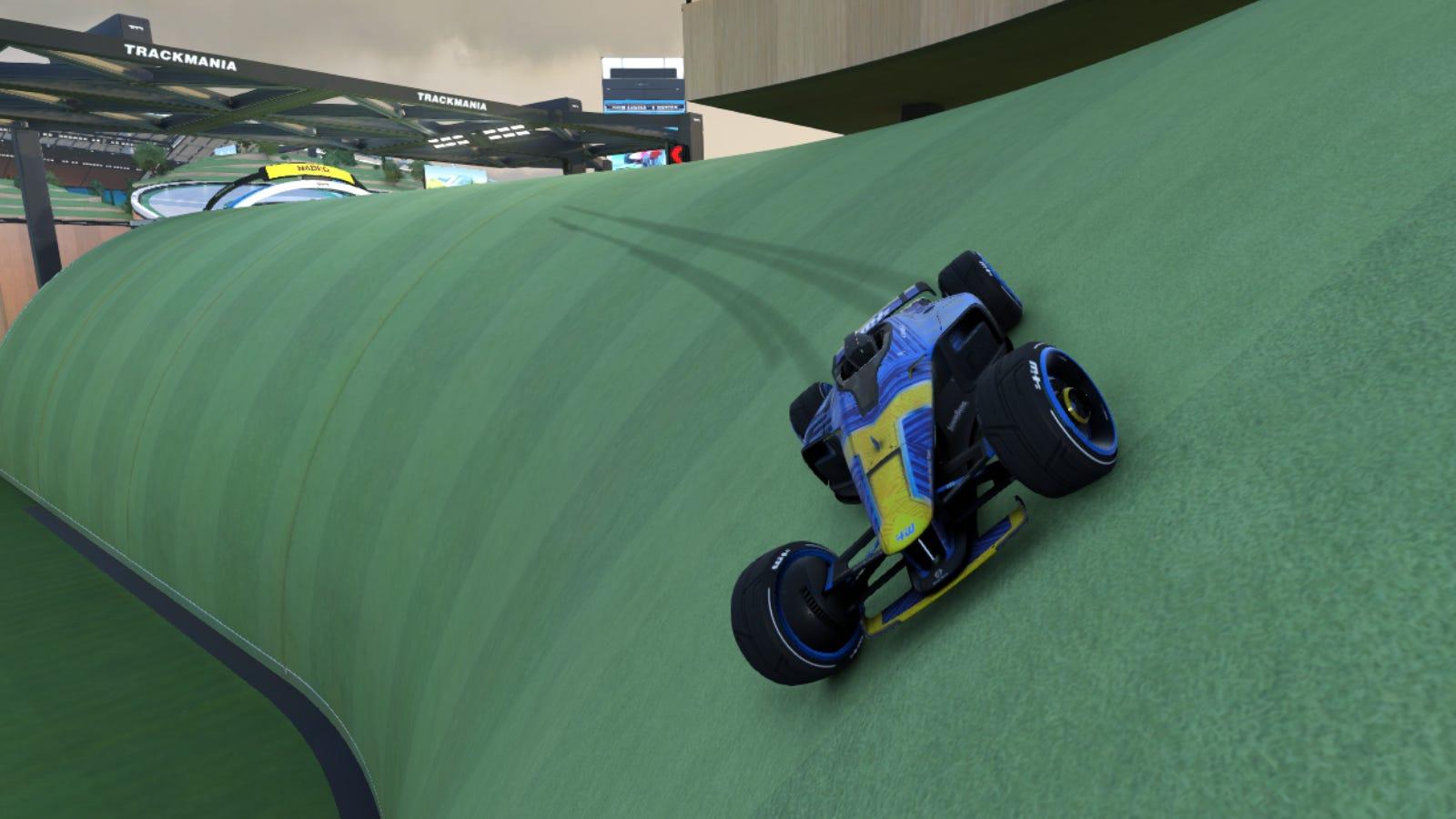 Course de voitures le long d'une colline herbeuse dans 'Trackmania'