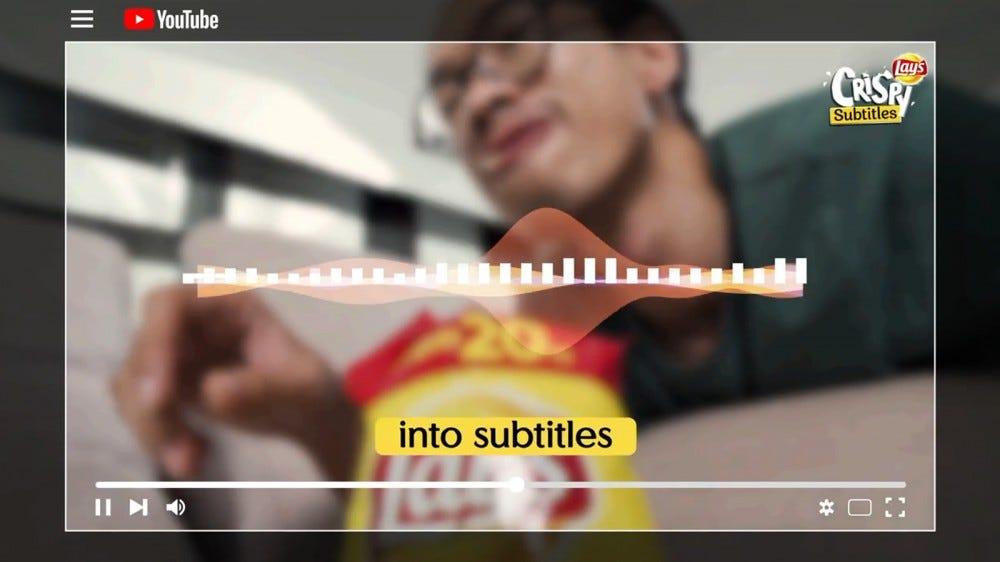 Un homme mange des chips de Lay en regardant YouTube.
