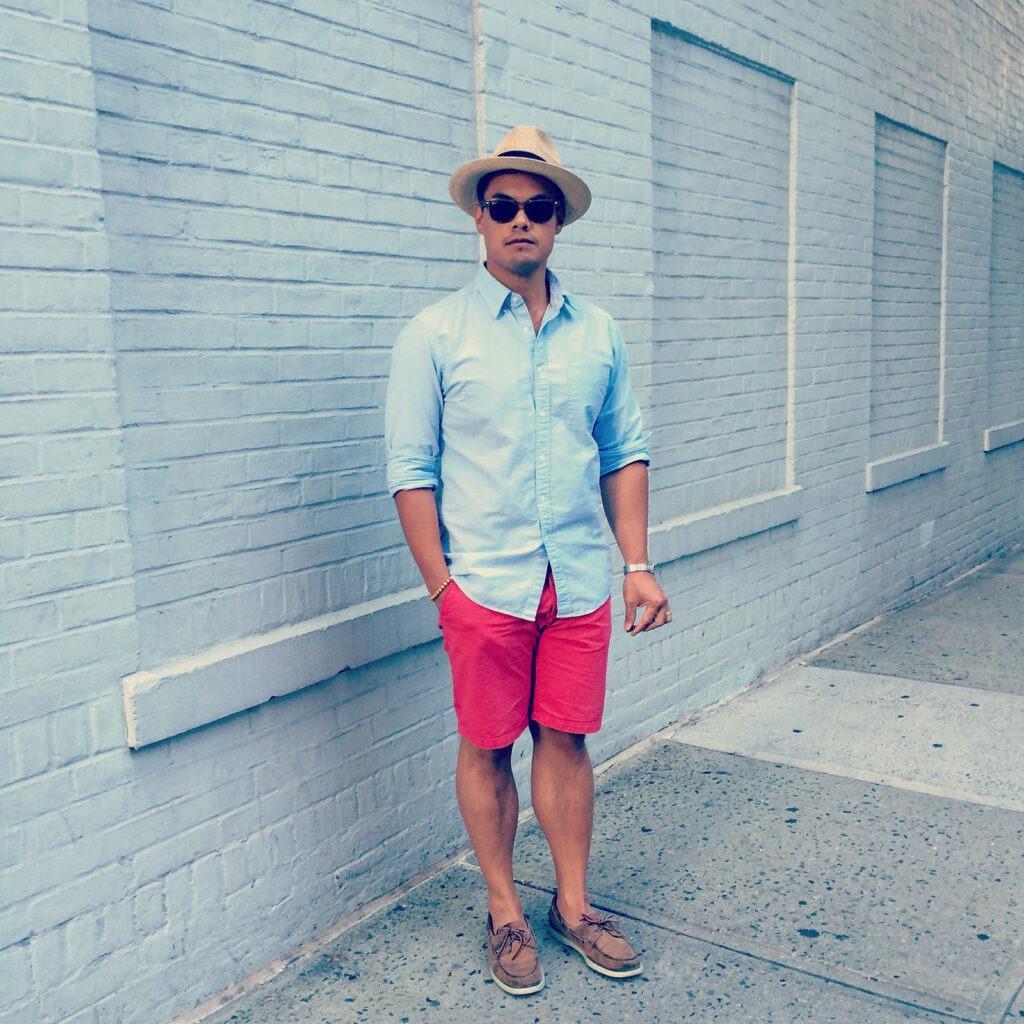 Homme portant une chemise oxford bleue avec un short rouge et un chapeau panama
