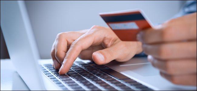 Une personne détenant une carte de crédit ou de débit tout en tapant sur un ordinateur portable.
