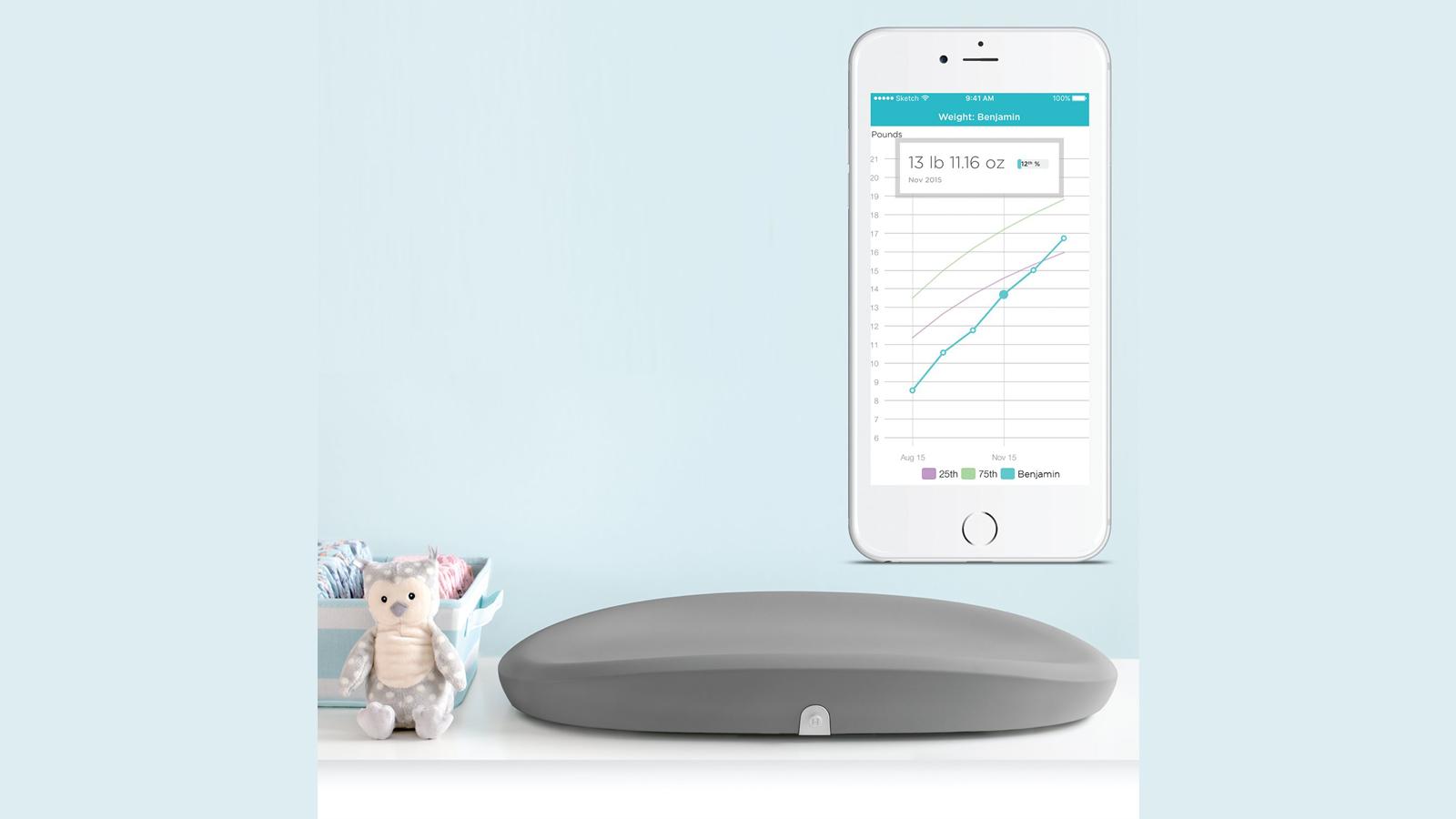 Hatch Baby Grow Smart matelas à langer sur la table à côté de jolis jouets pour bébé et application mobile compagnon sur smartphone