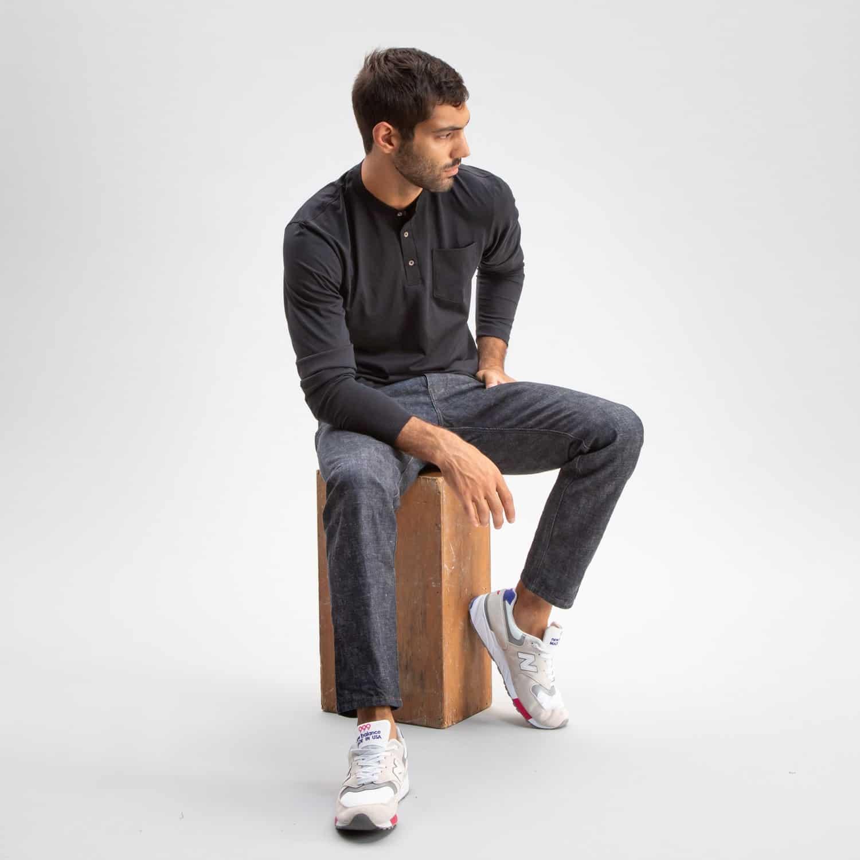 Homme assis portant un pantalon charbon et henley charbon de Todd Shelton