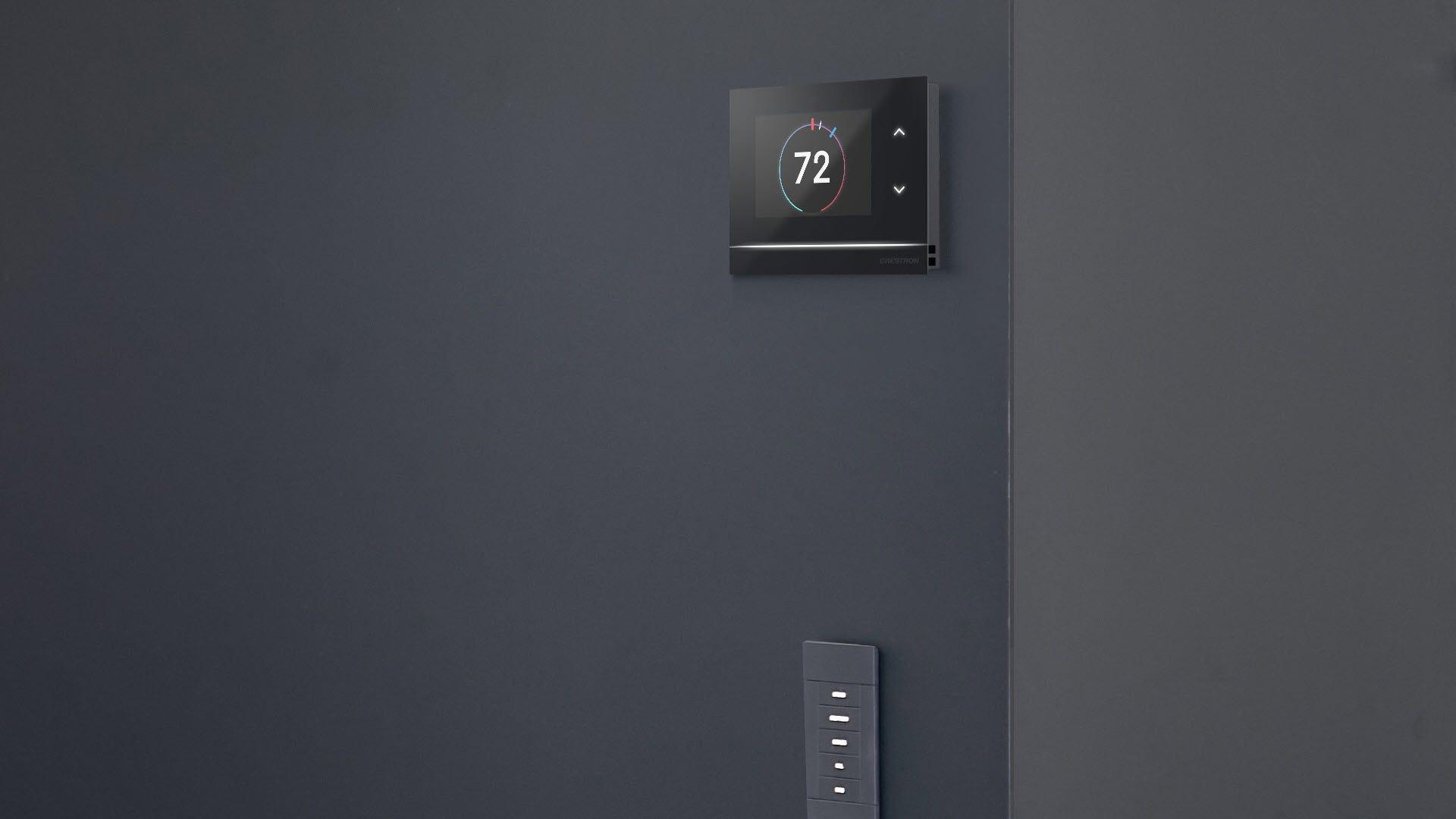 Un thermostat Crestron au-dessus d'un interrupteur d'éclairage