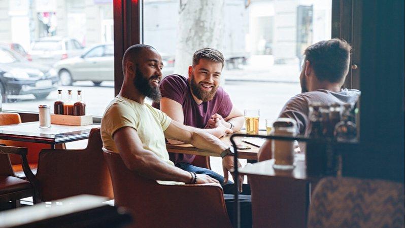3 hommes assis à une table de café à l'intérieur en riant