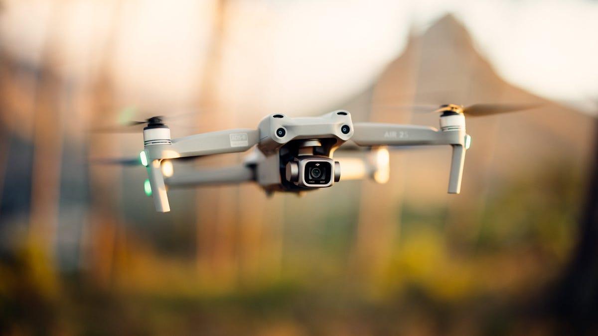 Un drone DJI Air 2S flottant dans un champ agricole.