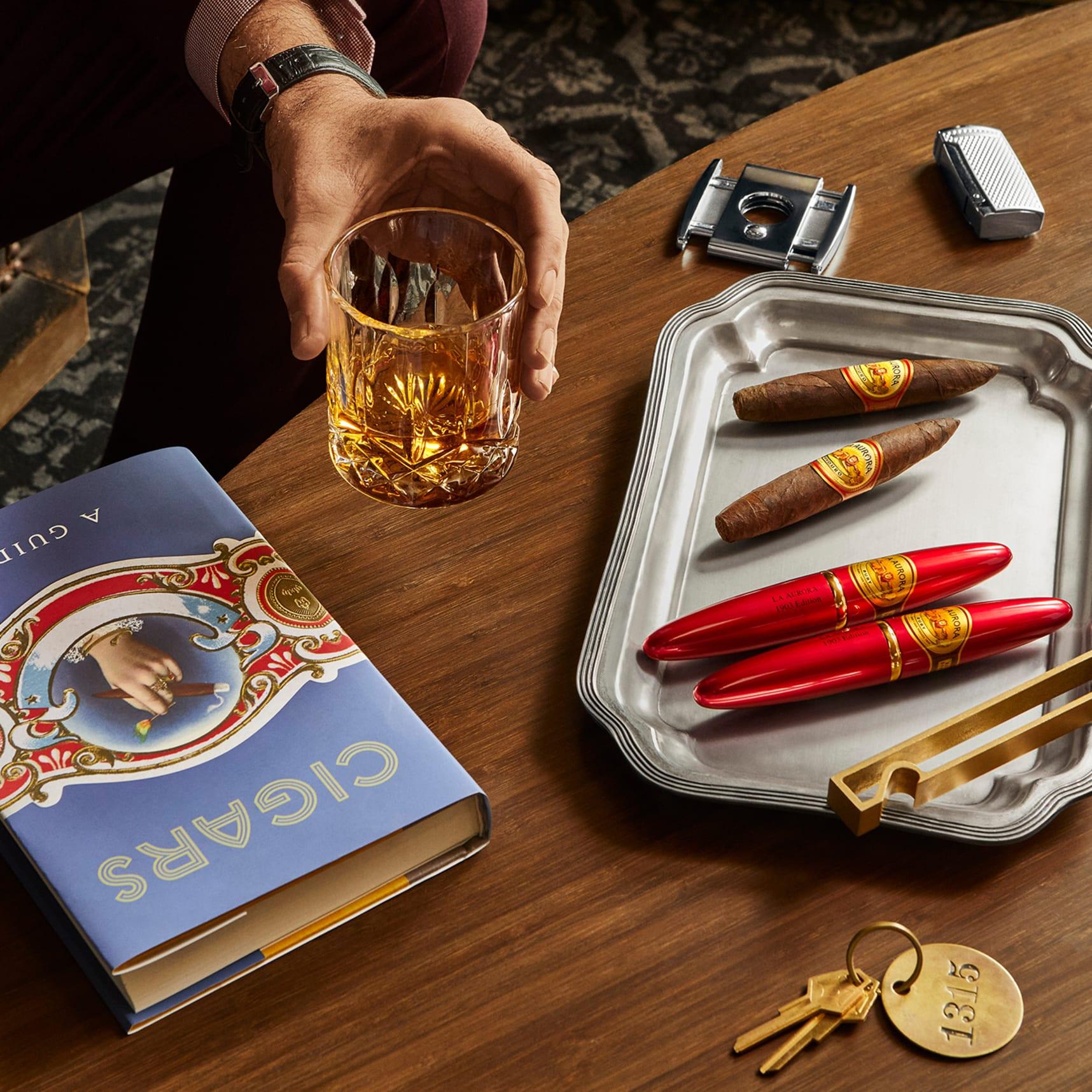 Gros plan du plateau avec des tubes de cigare rouge et la main de l'homme tenant le verre de bourbon à côté du livre de cigares