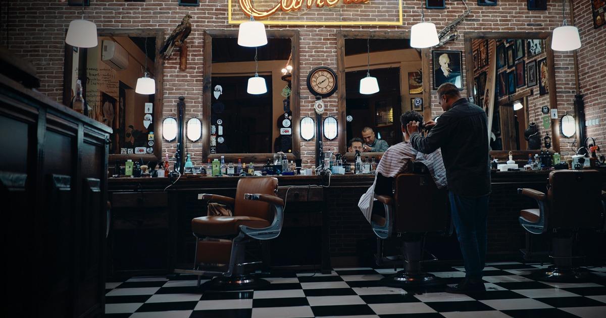 salon de coiffure faiblement éclairé avec un coiffeur et un client