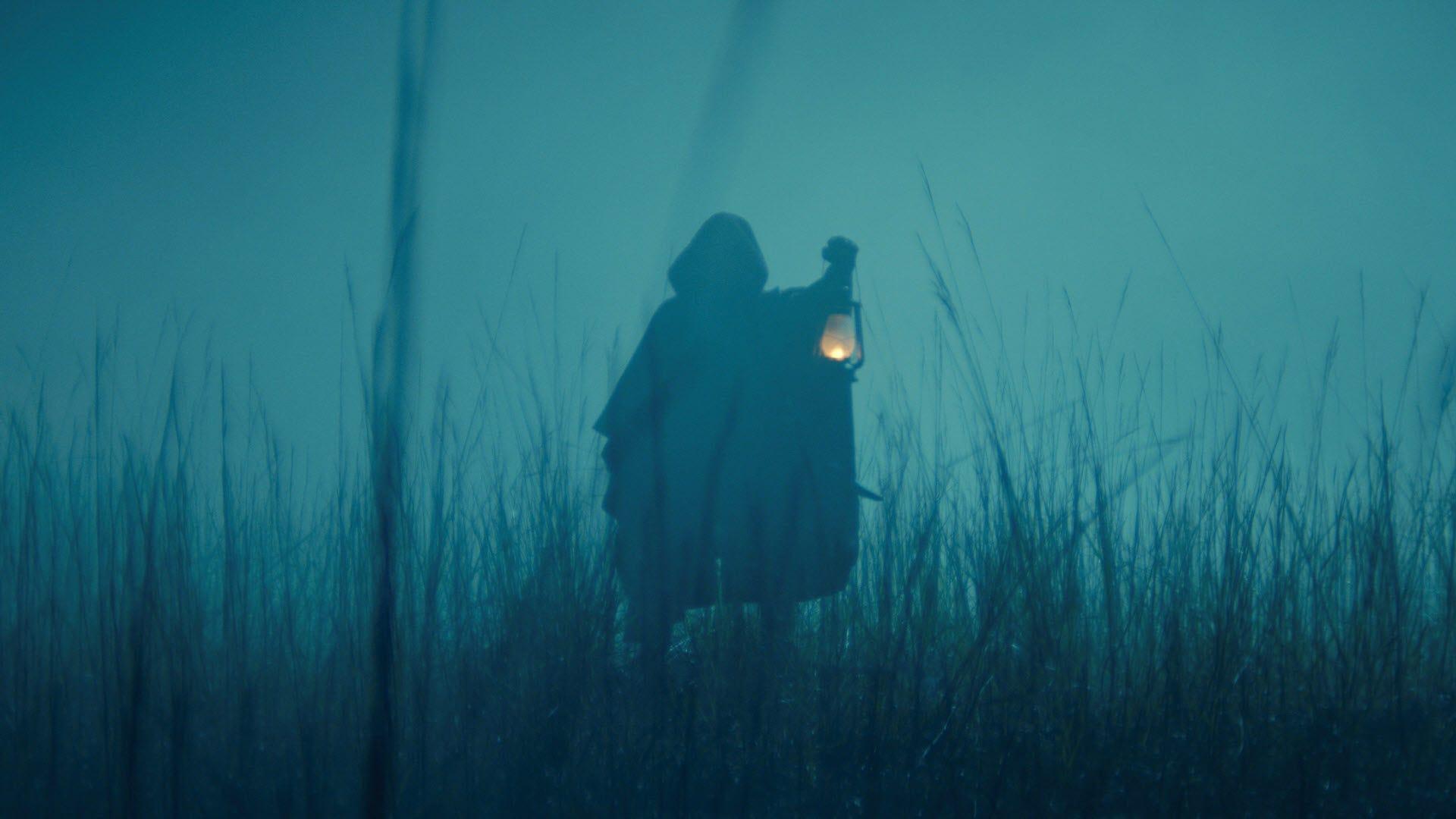 Une figure cachée dans l'ombre tenant une lanterne.