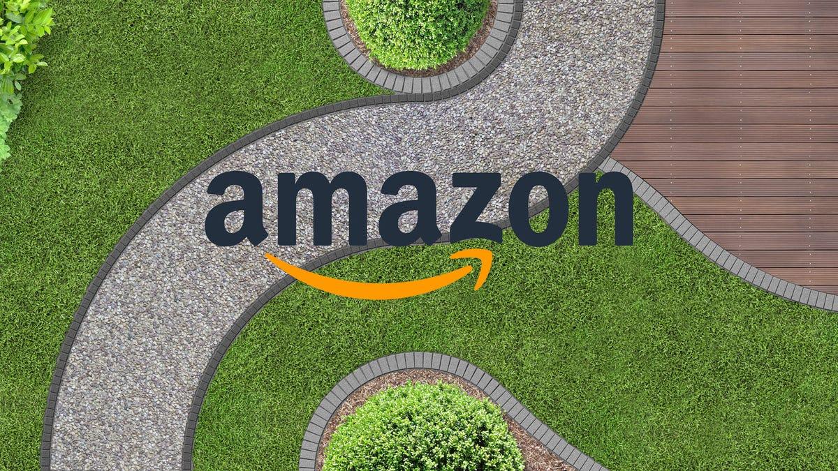 Un logo Amazon au-dessus d'un trottoir serpentant à travers un jardin.