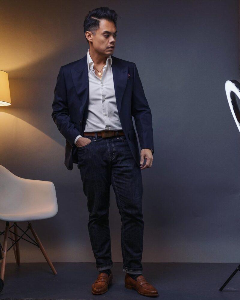 homme en veste marine, chemise blanche, jean bleu foncé et mocassins marron