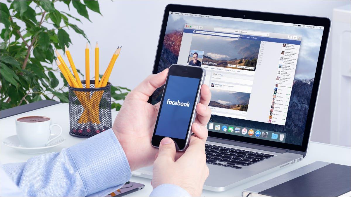Mains tenant un smartphone devant un ordinateur portable avec Facebook ouvert